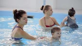 mesi dell anno : Happy middle-aged mother swimming with cute adorable baby in swimming pool. Smiling mom and little child, newborn girl having fun together. Active family spending leisure and time in spa hotel.