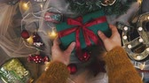 balicí papír : Christmas gift giving - someones hand in red knitted sweater making bow on red box with present, banner with copy space