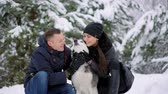 alaskan : Family portrait of cute happy couple hugging with their alaskan malamute dog licking mans face. Funny puppy wearing santa christmas deer antlers and kissing woman. Freedom lifestyle pet lovers. Stock Footage