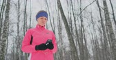 kocogás : A young female on the morning jog holds in her hands a smartphone picks a music track for training. Winter run. Use modern gadgets and training applications