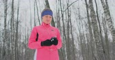 kocogás : A young woman on the morning jog holds in her hands a smartphone picks a music track for training. Winter run. Use modern gadgets and training applications