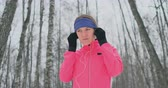 kocogás : The woman before the morning winter jog inserts headphones in the ears and is preparing to run through the natural Park in slow motion. Listening to music while running. Learn foreign languages