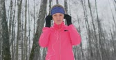kocogás : The female before the morning winter jog inserts headphones in the ears and is preparing to run through the natural Park in slow motion.