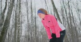 kocogás : A young woman on a morning jog in the winter forest was tired and stopped to rest and ran on. He recovered his strength and overcame fatigue and continued to run. Perseverance and overcoming weakness. Striving forward. Slow motion. Healthy lifestyle Stock mozgókép
