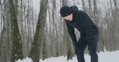 voorwaarden : A young man on a morning jog in the winter forest was tired and stopped to rest and ran on. He recovered his strength and overcame fatigue and continued to run. Perseverance and overcoming weakness. Striving forward. Slow motion. Healthy lifestyle