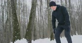 kocogás : A young man on a morning jog in the winter forest was tired and stopped to rest and ran on. He recovered his strength and overcame fatigue and continued to run. Perseverance and overcoming weakness. Striving forward. Slow motion. Healthy lifestyle