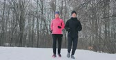 kocogás : Young man and woman on a morning run in the winter forest. A woman in a loose jacket a man in a black jacket is running through a winter park. Healthy lifestyle happy family. Stock mozgókép
