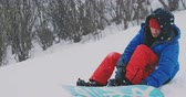 один человек : The man sitting in the snow zipper boots snowboard Стоковые видеозаписи