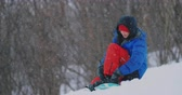 eğlence peşinde : A man in red pants sitting on the snow fastens snowboard shoes and a blue jacket on the ski slope
