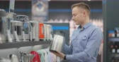 Young handsome man chooses an electric kettle to buy. Inspects the device, examines the price tags and the characteristics of the model. Stock mozgókép