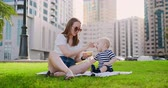 pequeno : Young mom with baby sitting on the grass in the Park eating lunch