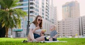 neşe : Young mom with baby sitting on the grass in the Park eating lunch
