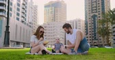 neşe : Family sitting on the grass in the city laughing with a small child. Stok Video