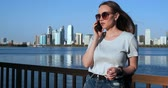 kurye : Young beautiful girl standing on the waterfront against the city talking on the phone
