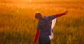 fingir : Little superhero boy in the field at sunset fantasizes and dreams.