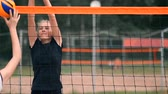 ismeretlen : SLOW MOTION, CLOSE UP, LOW ANGLE: Unrecognizable young female hands playing volleyball at the net. Offensive player spikes the ball and the opponent blocks it right above the net during a tournament.