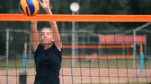 неузнаваемый : SLOW MOTION, CLOSE UP, LOW ANGLE: Unrecognizable young female hands playing volleyball at the net. Offensive player spikes the ball and the opponent blocks it right above the net during a tournament.