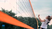 с шипами : Four girls volleyball players play on the beach in the summer participating in the tournament in slow motion on the sand.
