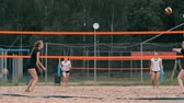 удара : Young woman playing volleyball on the beach in a team carrying out an attack hitting the ball. Girl in slow motion hits the ball and carry out an attack through the net