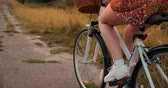 lovaglás : Smiling happy girl in dress and hat riding retro bicycle in the park and looking at camera Stock mozgókép