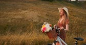 vadvirágok : Young smiling blonde in hat and dress walking in dress with bike and flowers in basket.