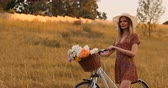 vadvirágok : A beautiful woman with a Bicycle in a hat and a light summer dress comes with flowers in a basket and smiles.