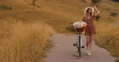 lovaglás : Middle plan girl in dress goes with bike and flowers in the field.