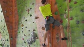agilitás : Climbing sport activity concept: Man climber on wall. Indoor climbing sport activity concept: man climber on artifical climbing wall Stock mozgókép