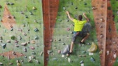 agilitás : Climbing sport activity concept: Man climber on wall. Indoor climbing sport activity concept: man climber on artificial climbing wall Stock mozgókép