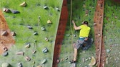 agilitás : Male climber climbs the cliff wall in the room reaching and gripping hold. A professional concentrated climber moves up the wall, the camera rises and lays down his movements. Boom follow camera