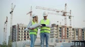 스톡홀름 : Business, building, industry, technology and people concept - smiling builder in hardhat with tablet pc computer along with woman with drawings of builders at construction site.