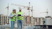 collega : Adult engineer man and architect woman uses a tablet in operation. Writes a message or checks a drawing. Against background is building.