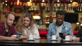 collega : Two men and Two women multi-ethnic couples sit in a cafe and look at the screens of smartphones and discuss Stockvideo