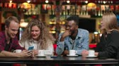 zenci amerikalı : African-American man with a girl looking at a smartphone and talking while sitting in a coffee and drinking coffee, friends a group of people in a restaurant Stok Video
