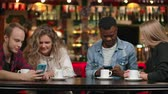 mestiço : Group of friends at a bar drinking coffee and discussing while looking at the screen of a smartphone Stock Footage