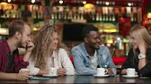 memória : Student meeting in a restaurant and cafe. A man in a shirt tells a story to friends, two girls and an African American are listening and laughing. A group of friends spend time together.