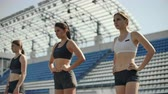 mei : Female runners at athletics track crouching at the starting blocks before a race. In slow motion