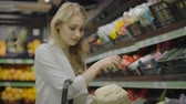 решить : Young beautiful brunette girl in her 20s picking out napa cabbage and cauliflower and putting them into shopping cart at the fruit and vegetable aisle in a grocery store. Стоковые видеозаписи