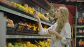 решить : Young Woman Choosing Ripe Mangoes in Grocery Store. Vegan Zero Waste Girl Buying Fruits and Veggies in Organic Supermarket and Using Reusable Produce Bag. 4K Slow motion. Стоковые видеозаписи