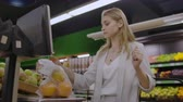 kruidenier : A blonde girl in a supermarket weighs oranges on an electronic scale pressing the display standing with a basket in her hands. Stockvideo