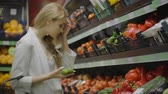 nadenken : A woman selecting taking cucumbers, vegetables in a supermarket. shopping selection buying fruit, vegetable. Young girl, woman choosing and buying tomatoes and vegetables. health shopping girl Stockvideo