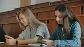 друзья : Multi Ethnic Group of Students Using Smartphones During the Lecture. Young People Using Social Media while Studying in the University.