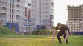 impegno : An athlete doing extreme push up  using backflips and pushups at sunset in slow motion the background of the city