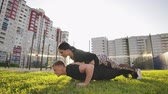 dát : Guy and girl push-ups outdoors. Male and female doing exercises together outdoor. Couple doing sport keeping the body in tension, leaning on the extended arms.