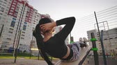 dýchat : Doing twisting crunches. Serious confident sporty young woman sitting on wooden bench and doing twisting crunches at sports ground. Dostupné videozáznamy