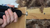 stolarz : Worker fixes the board to the wall using electric screwdriver. The mineral wool under the board. Close up.