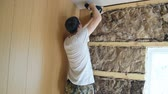 stolarz : A young white man tightening the screw using the screwdriver for fixing lining boards. The rock wool on the wall of the room. Wideo