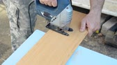 stolarz : Man with electric jigsaw cutting a piece of molded board.