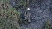 начало : The firefighter goes through the burned area. Ashes under the feet of the fireman.