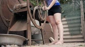 elegantní : Young girl barefoot cuts grass for the animals with manual mechanical cutting. Rotating mechanical wheel the cut grass falls into metal container. The rotation of the gears. Outdated equipment.